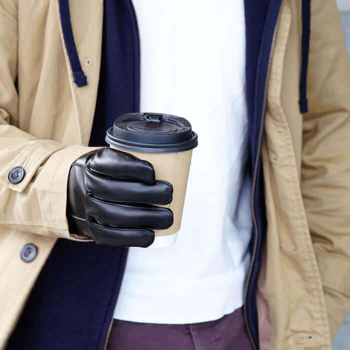 レザーグローブでホットコーヒーを持つ
